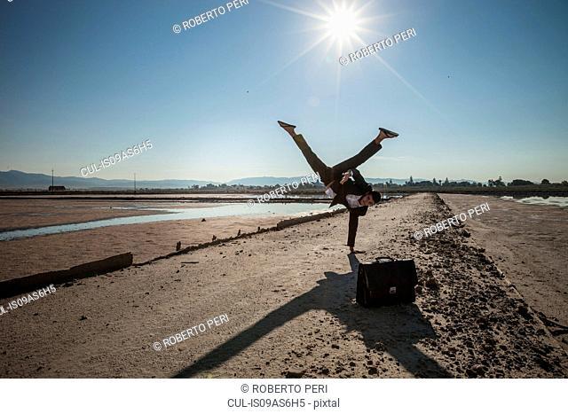 Mid adult businessman doing handstand on beach