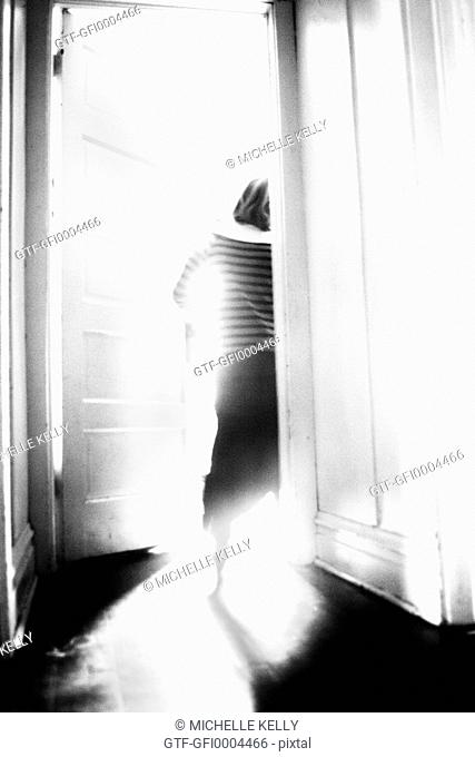 Black and whilte photo of Girl exiting through door
