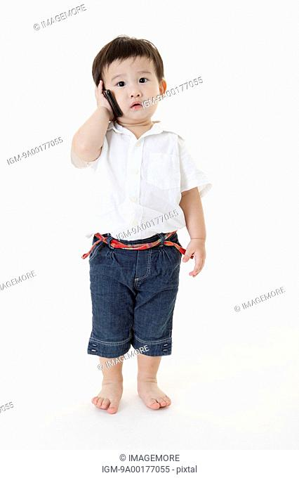 Baby boy standing and holding mobile phone