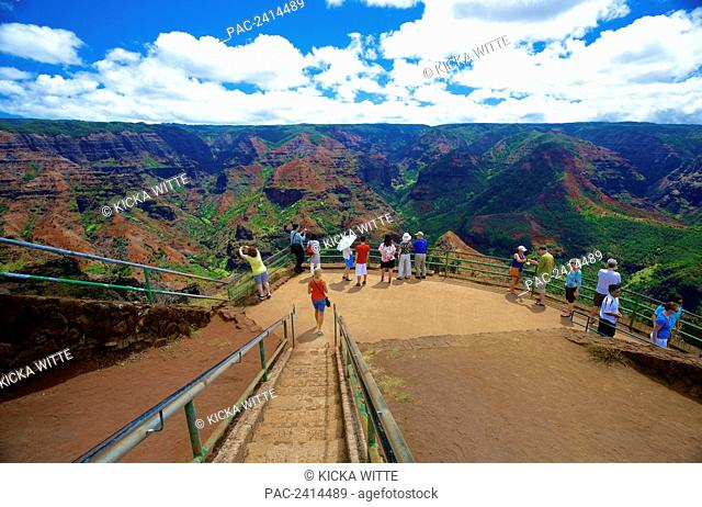 Tourists gather to view the mountainous landscape of Waimea Canyon State Park; Kauai, Hawaii, United States of America