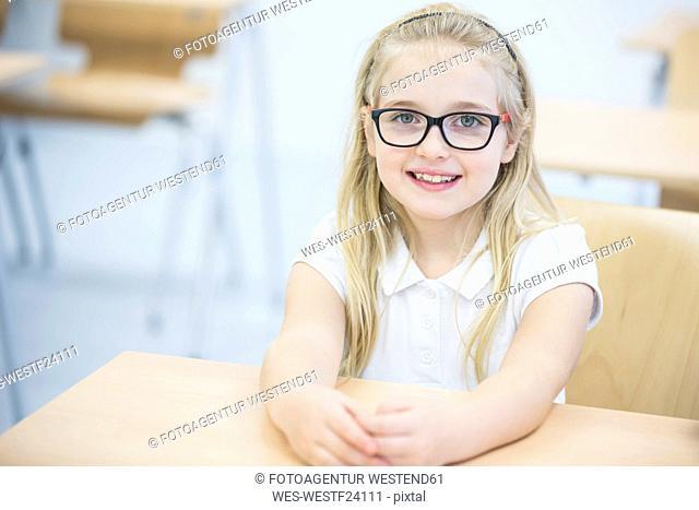 Portrait of smiling schoolgirl in class