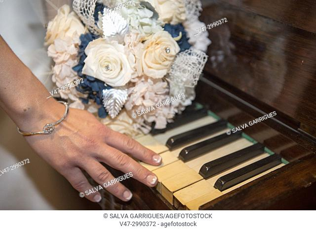 Close-up of the bride's stroking the keys of a piano
