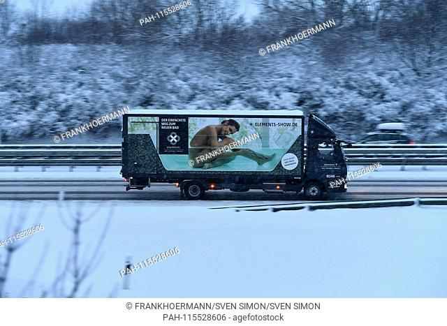 Truck with advertising for bathrooms shows naked woman. Snow chaos on the streets of Bavaria - as here on the A94 motorway in Muenchen Riem is the busy traffic