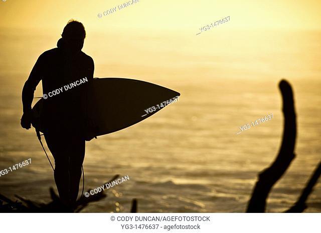 Surfer walking along debris ridden shore at Rincon Point, California