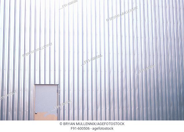 Partially painted door and aluminum sided factory building