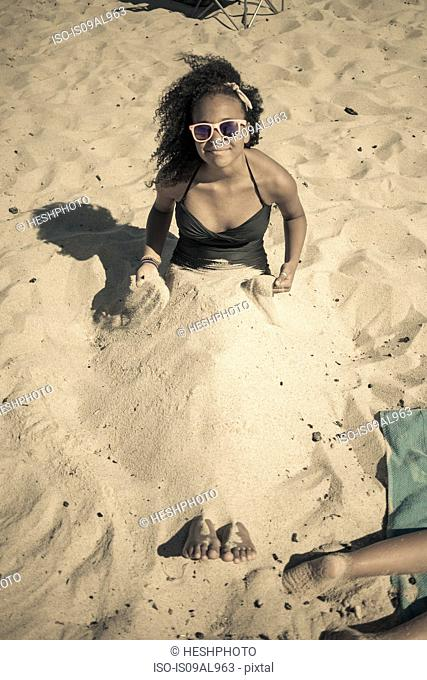 Girl buried in sand on beach, Truro, Massachusetts, Cape Cod, USA