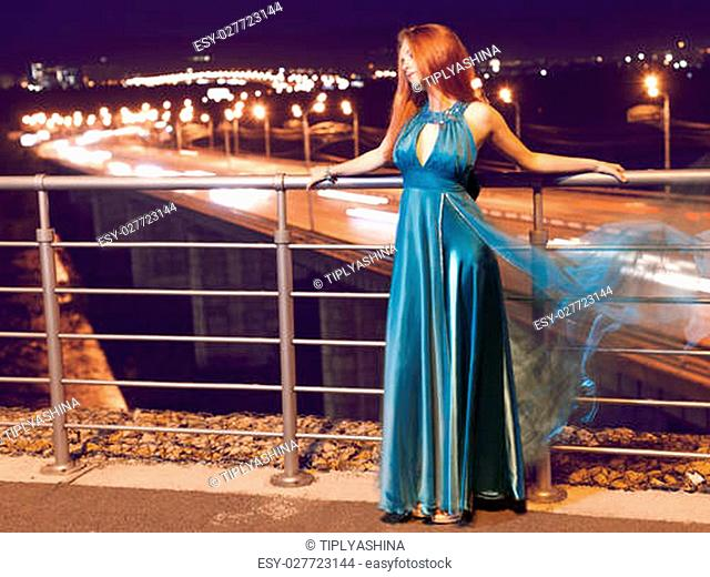 Young beauty woman in fluttering blue dress outdoor
