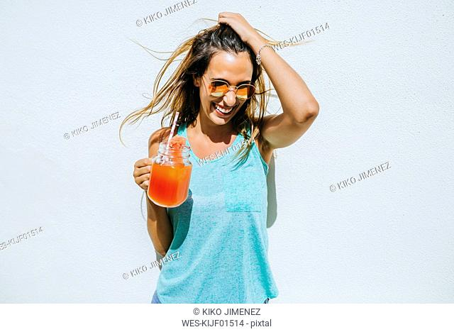 Happy young woman holding watermelon drink in front of white wall