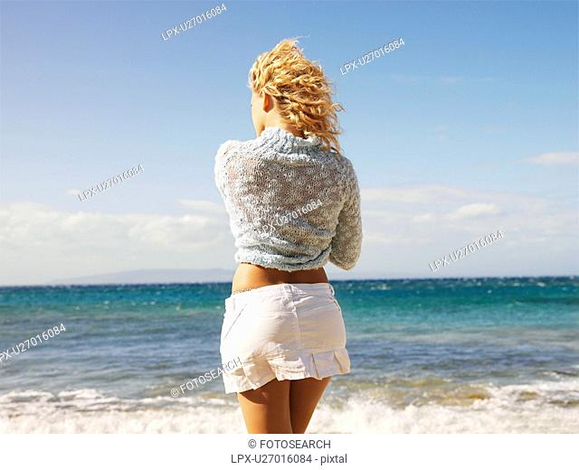 Back view of young blond woman standing at water's edge on Maui, Hawaii beach gazing at the ocean