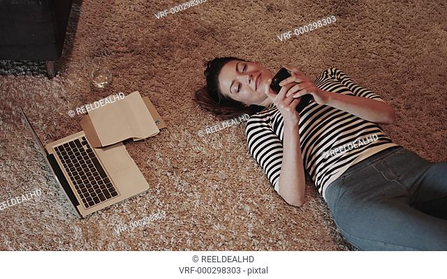 Young adult woman on floor with smart phone