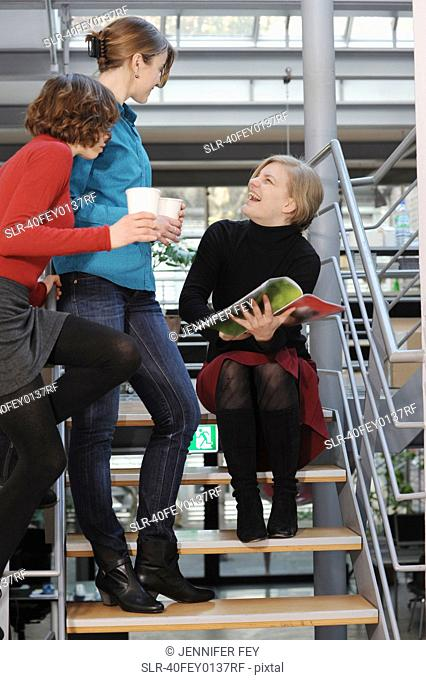 Businesswomen talking on steps in office