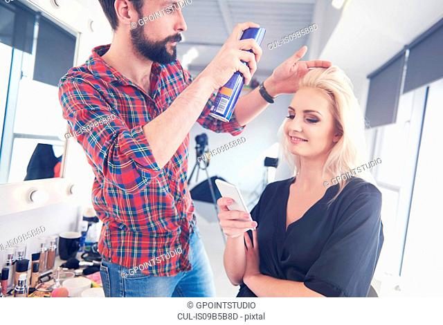 Male hairdresser putting hairspray on model for photo shoot