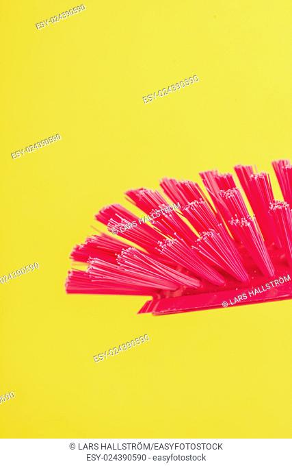Dish brush in close-up. Red plastic dishwashing equipment