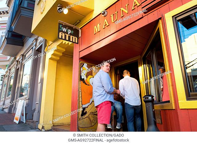 A doorman is checking the IDs of two men entering the Mauna Loa Club in San Francisco, California, October 8, 2016