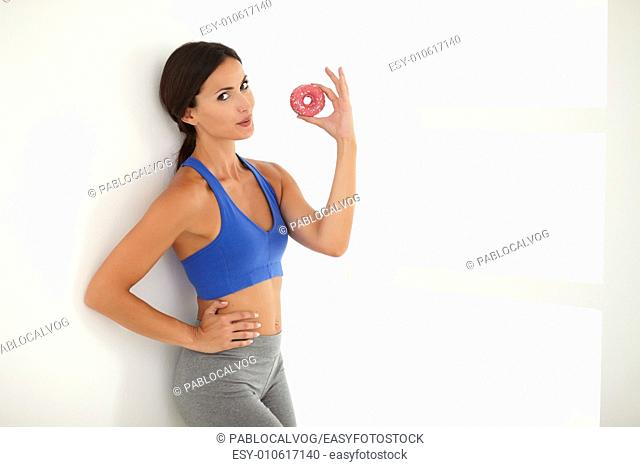 Fit woman with slim figure dieting and with temptation while looking at you