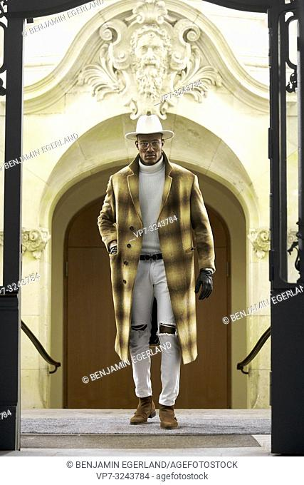 stylish wealthy man wearing expensive clothes, standing in door frame, in city Munich, Germany