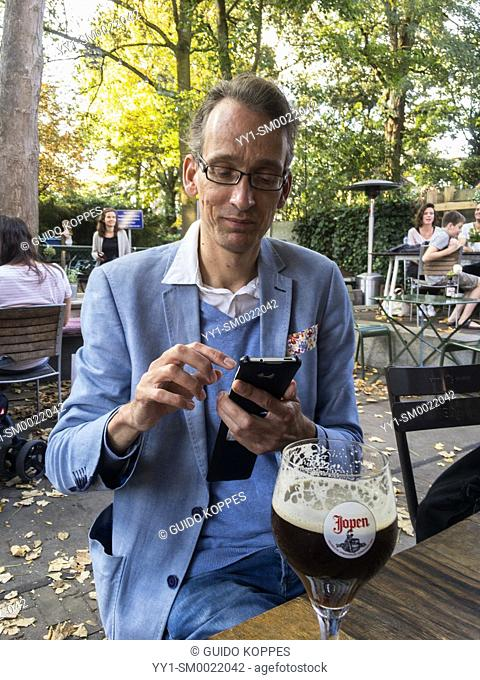 Tilburg, Netherlands. Mid adult male using his smartphone while drinking a beer and having a conversation. Friendship is often celebrated in cafe's and...
