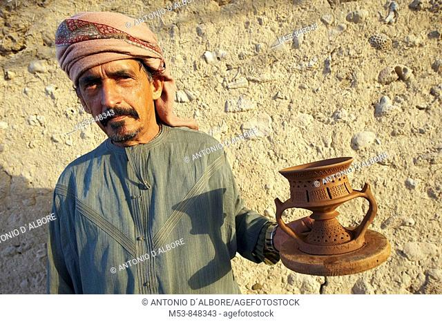 an arabic craftsman show an handmade clay candle holder dubai united arabic emirates middle east