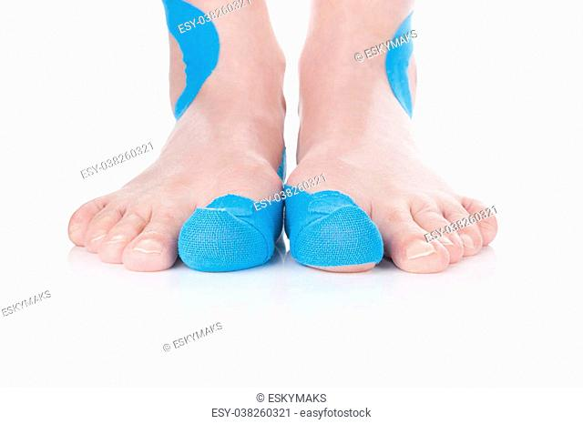 Kinesio tape on female foot isolated on white background. Chronic pain, alternative medicine. Rehabilitation and physiotherapy