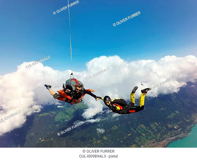 Portrait of tandem skydivers holding hands with female skydiver above clouds and landscape
