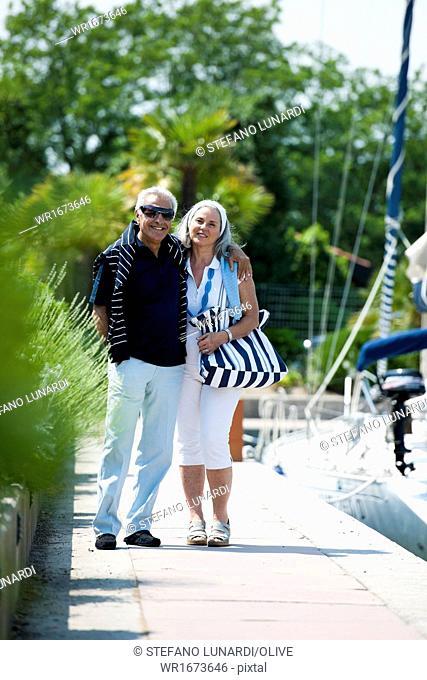 Mature couple enjoying a stroll at a marina