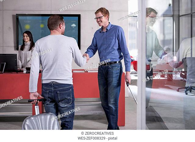Two smiling men shaking hands at reception area