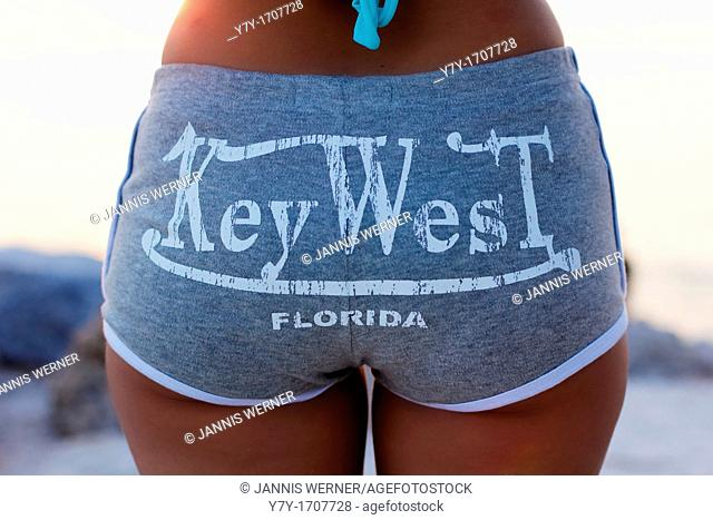 A tan young woman on the beach, seen from behind, wearing hot pants with the writing Key West, Florida across the back