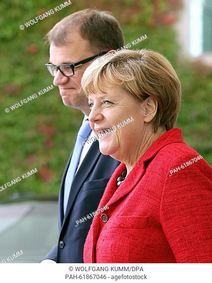 German Chancellor Angela Merkel (R) receives Finland's Prime Minister Juha Sipila with a military salute at the Federal Chancellery in Berlin, Germany