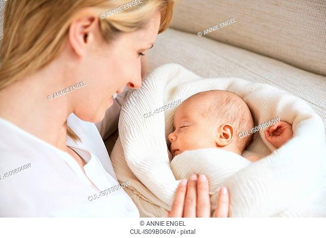 Mid adult woman gazing at baby daughter sleeping