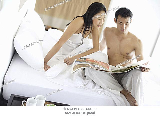 Couple sitting on bed, looking at newspaper