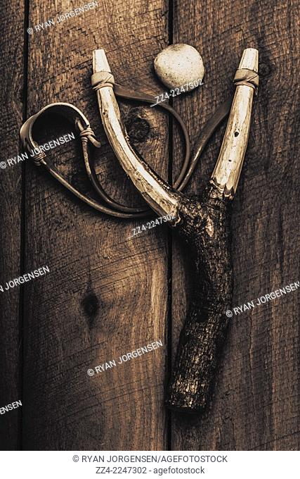 Vintage still life photograph of a toy slingshot on wooden cubby house floor in a nostalgic hit of revenge. Sticks and stones