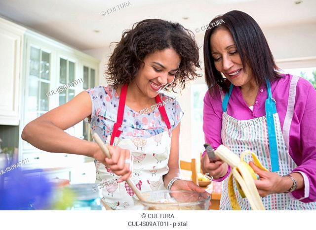 Mother and grown daughter, cooking in kitchen