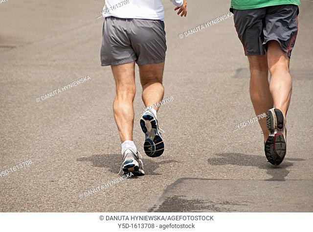 two men in shorts running the street, legs only, Geneva, Switzerland