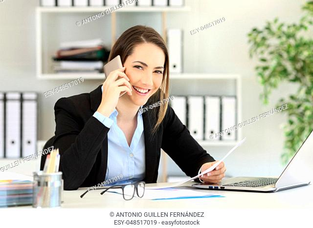 Happy office worker calling on phone looking at you at workplace