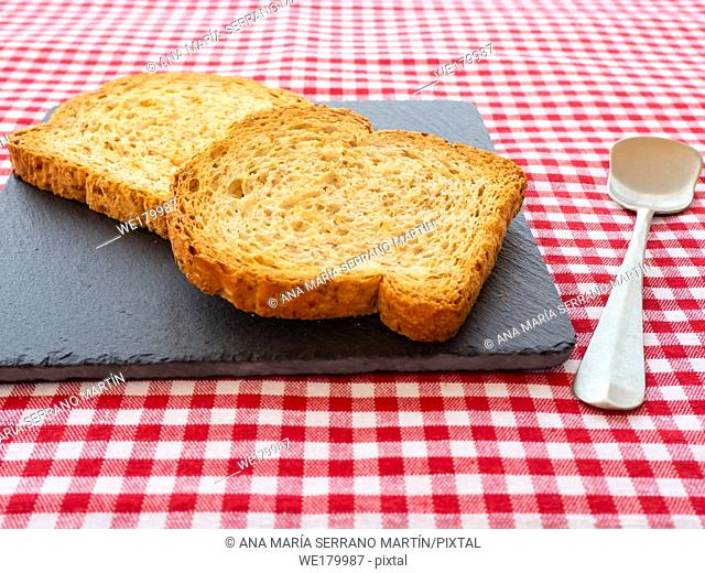 Two slices of toast on a slate plate, one old spoon and tablecloth vintage style