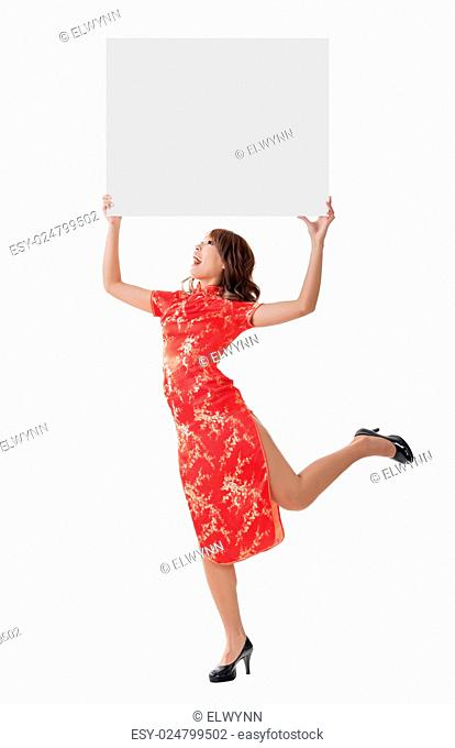 Attractive Chinese woman dress traditional cheongsam and hold blank board, full length portrait