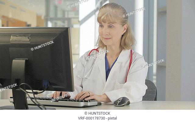Nurse recording patient data on hospital computer