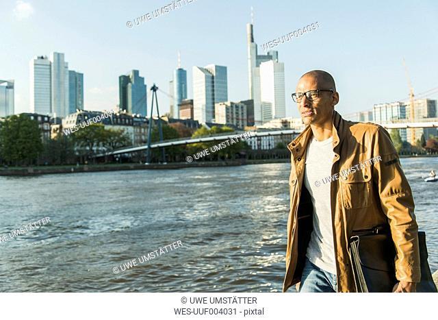 Germany, Frankfurt, man holding briefcase walking at the riverside
