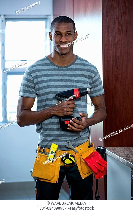 Smiling manual worker holding a drill machine