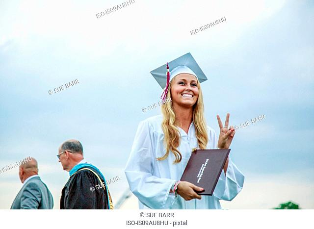 Young female graduate making peace sign at graduation ceremony