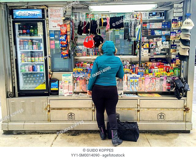 New York, USA. Customer and commuter in the Manhattan Subway buying candy and magazines in a platform store in a subway station