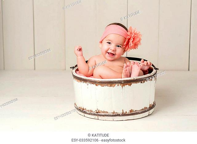 Six Month Old Baby Girl Sitting in a Vintage Wooden Bucket. She is Laughing and Wearing a Large Peach Colored Flower Headband