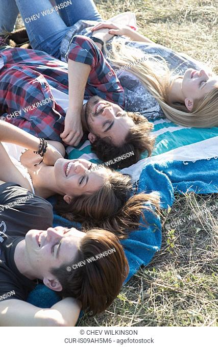 Four friends lying on blanket
