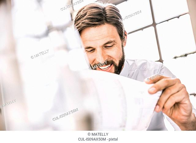 Bearded businessman looking down at paperwork smiling