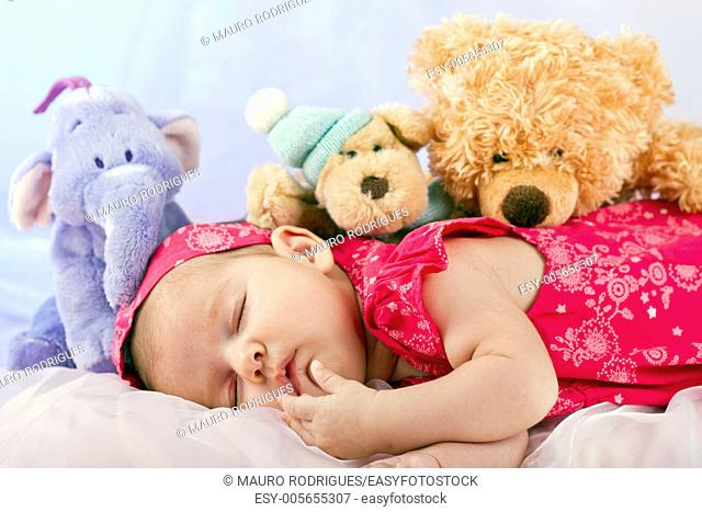 View of a newborn baby on smooth bed with stuffed toy sleeping