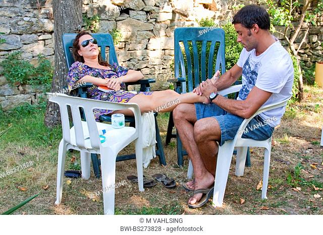man massaging the feet of his girl friend in the yard of a pilgrims's house, Spain, Basque country, Navarra, Trinidad de Arre, bask. Villava