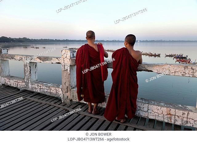 Myanmar, Mandalay, Lake Taungthaman. Two Buddhist monks promenade on U Bein teak bridge in Myanmar just after sunset