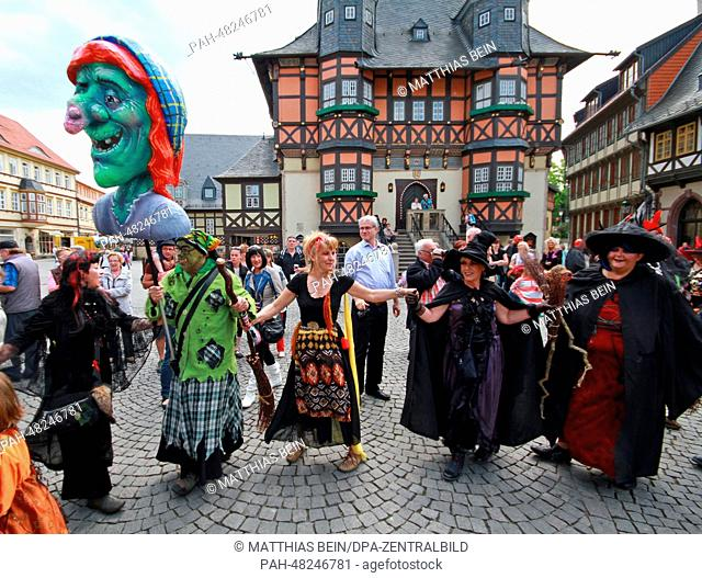 People dressed in devil and witch costumes to celebrate Walpurgis Night stand outside city hall in Wernigerode, Germany, 30 April 2014