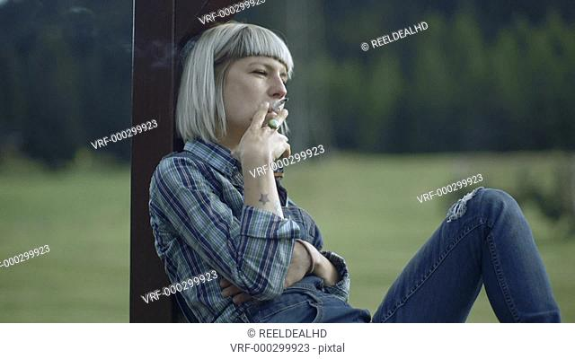 Female smoking in countryside
