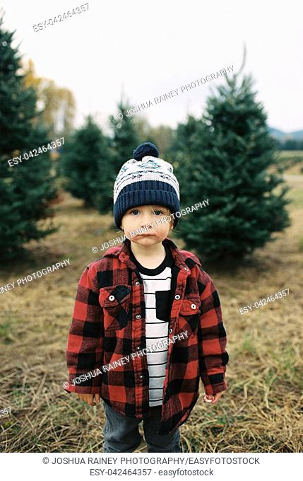 Cute two year old boy wearing a stocking cap in a winter or fall lifestyle portrait featuring the young kid in an image from a film scan